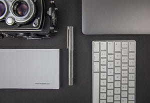 Flat lay image showing the Otto Hutt design 08 amongst other desktop items