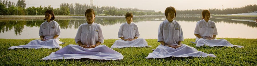 A group of Thai school children meditating outdoors