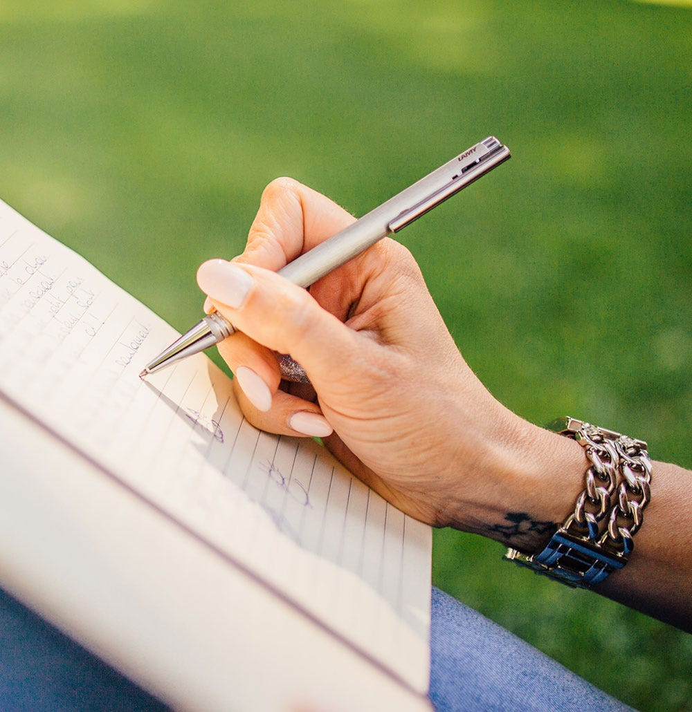 A lady's hand holding a ballpoint pen and writing