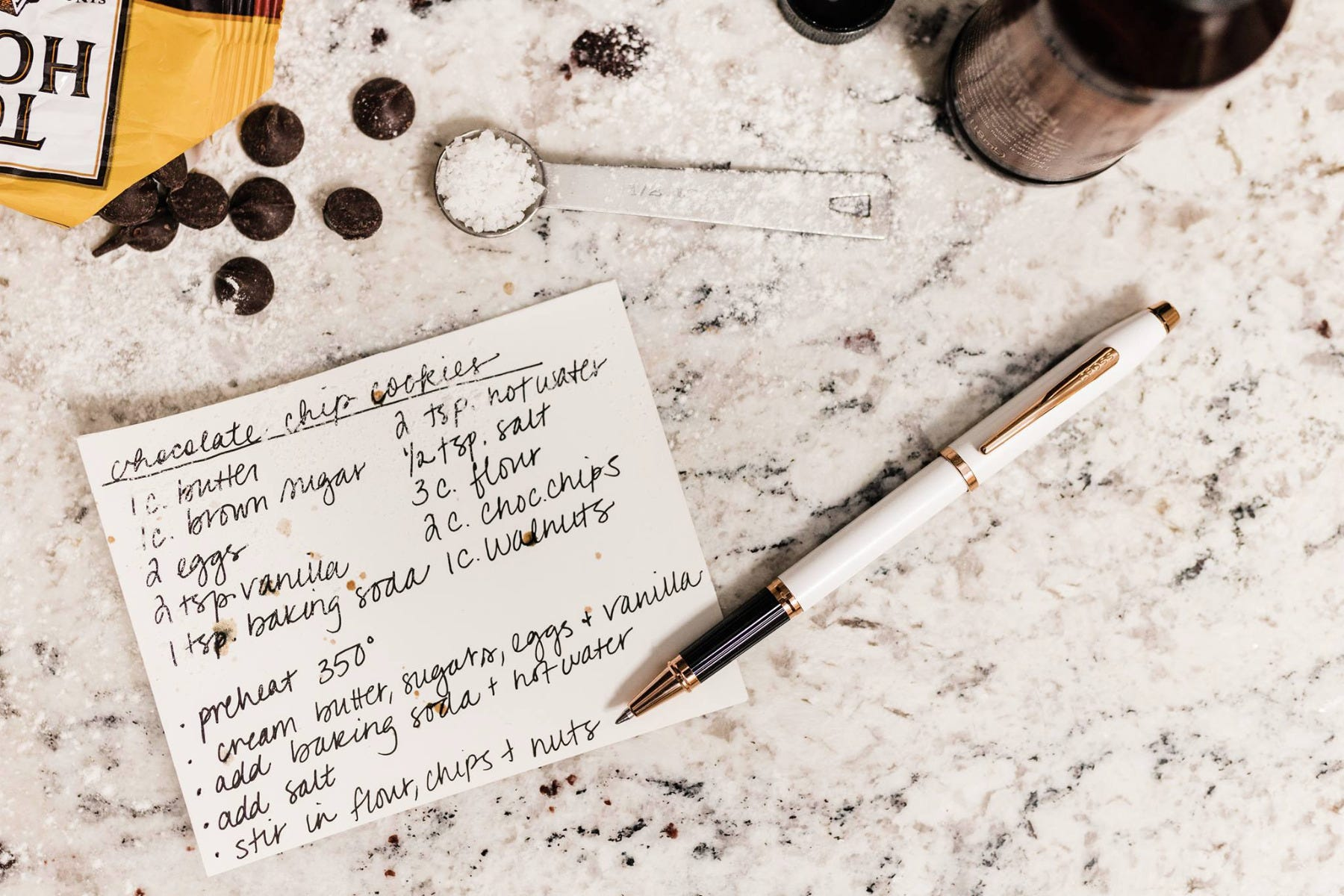 A Cross Century II white lacquer rollerball pen with a recipe card, surrounded by ingredients