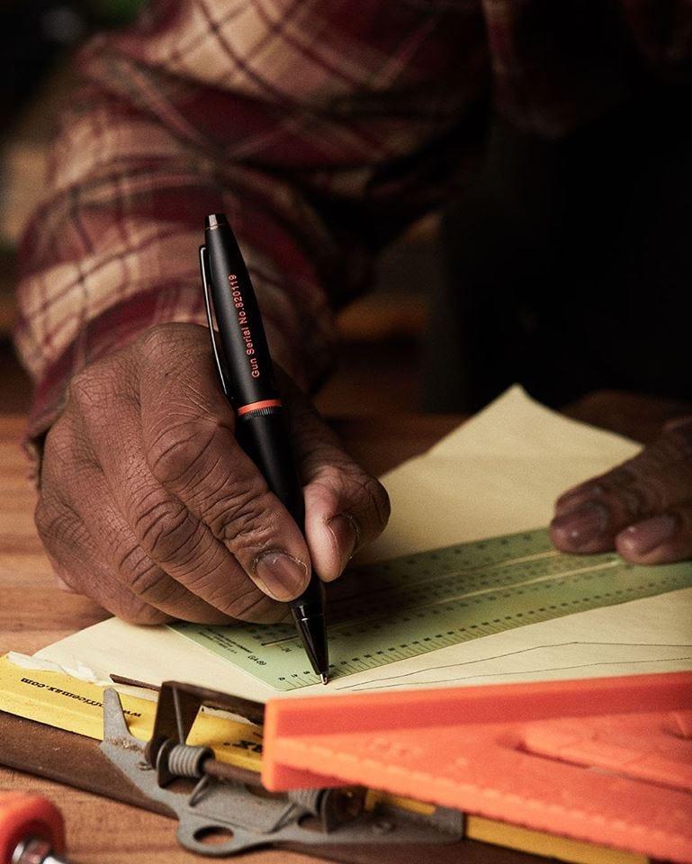 A man at a work desk using a Cross Calais Liberty United Ballpoint Pen